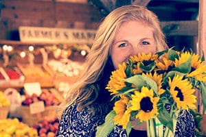 Woman holding sunflowers.
