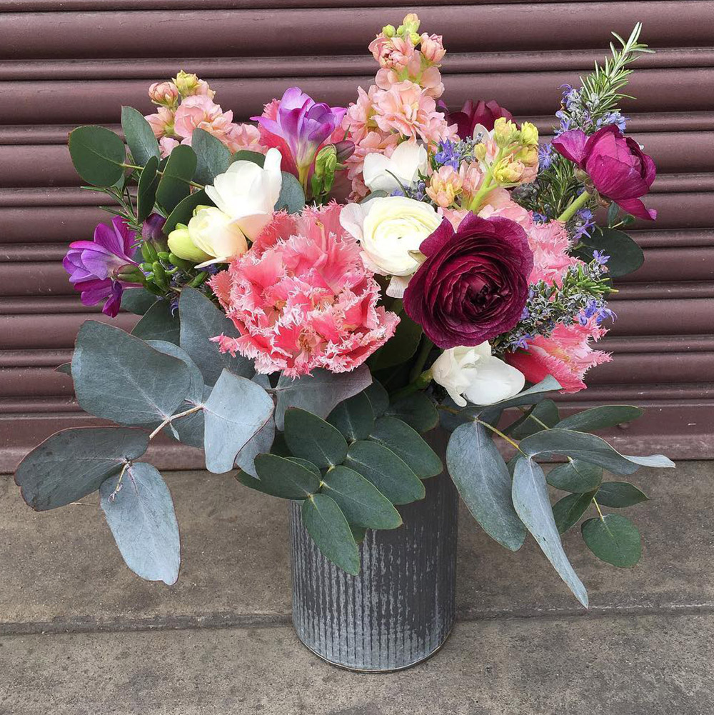 A metal vase filled with flowers arranged by Bloom Sacramento.