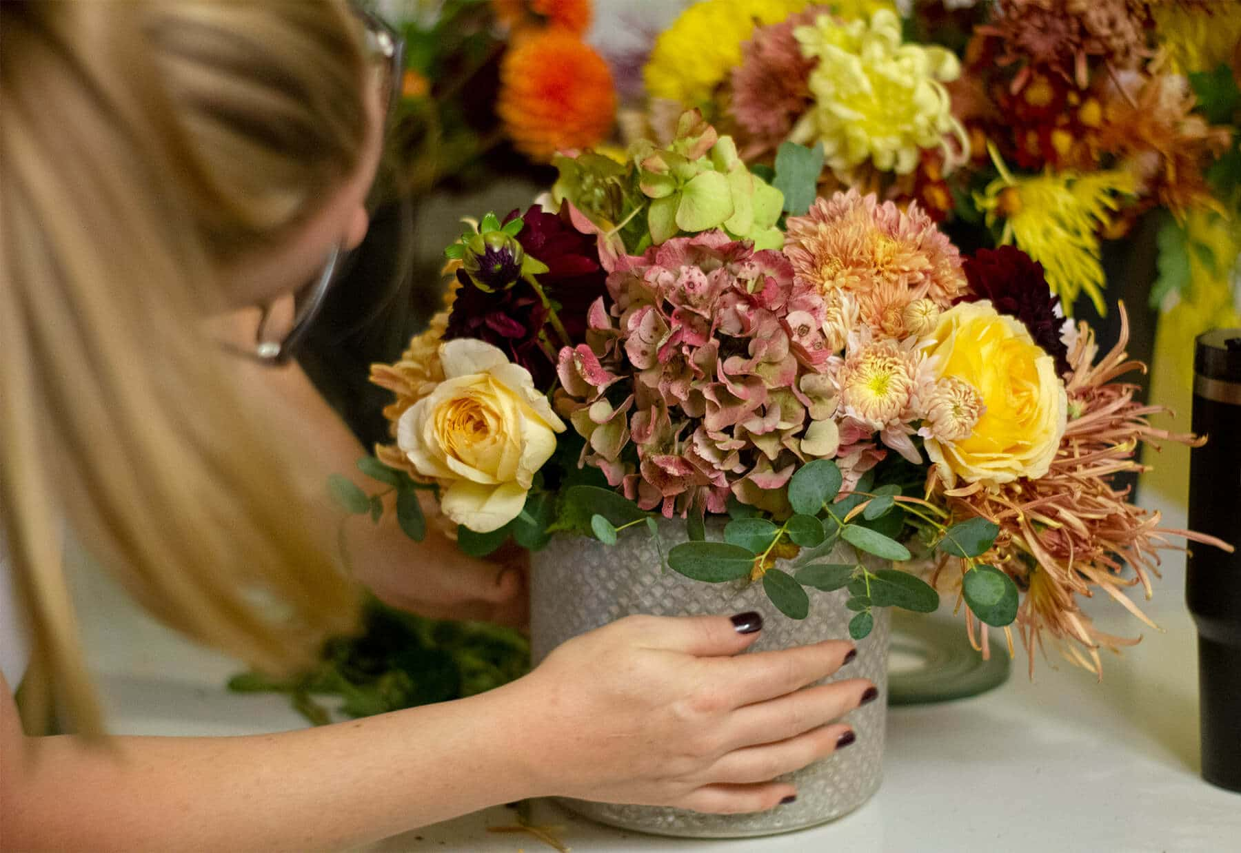 Amanda Kitaura of Bloom arranging flowers in a fall centerpiece.