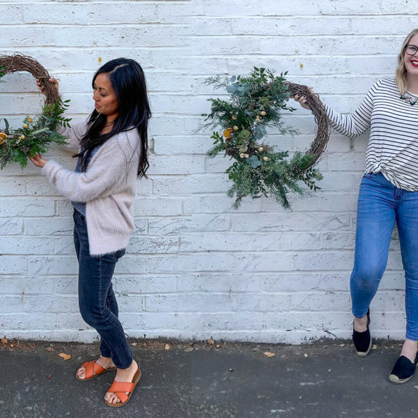 Two women stand in front of a brick wall, holding wreaths.