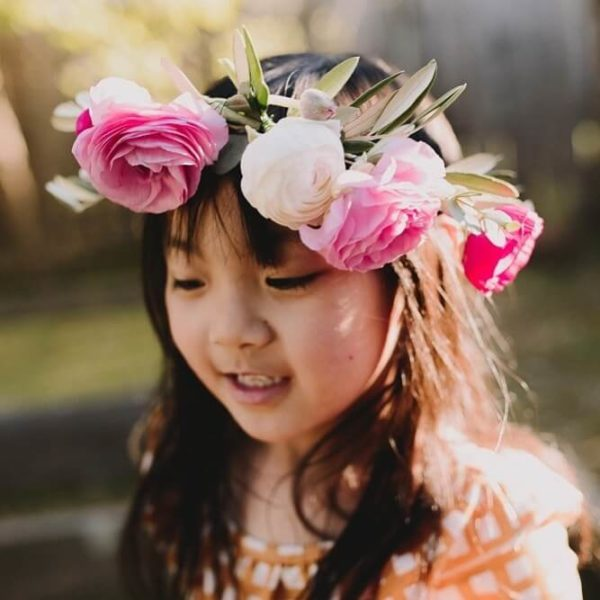 A child wears a flower crown kit from Bloom Sacramento.