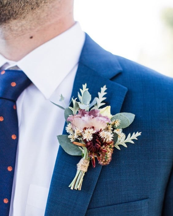 Man wearing blue suit wears boutonniere made by Bloom Sacramento